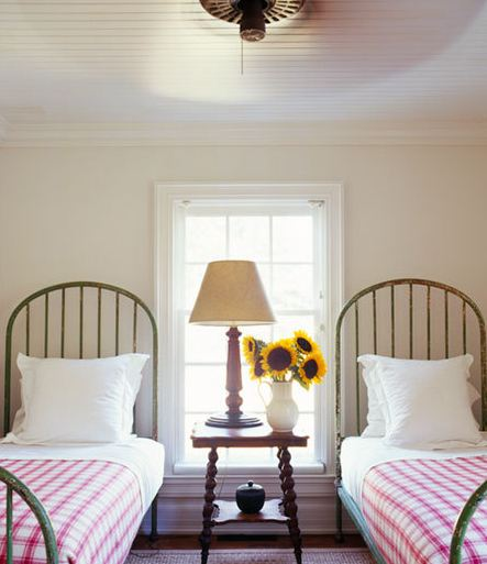 High arched iron beds, simple linens and fresh flowers....charming. via-cococozy